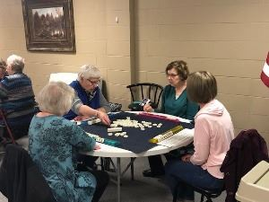 4 women sitting at a table playing Mahjong
